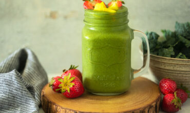 green smoothie in mug topped with chopped strawberries and mango