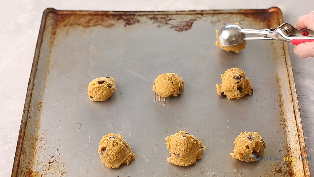 scooping cookie dough onto cookie sheet