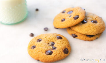 4 chocolate chip cookies on white background with glass of milk on the side