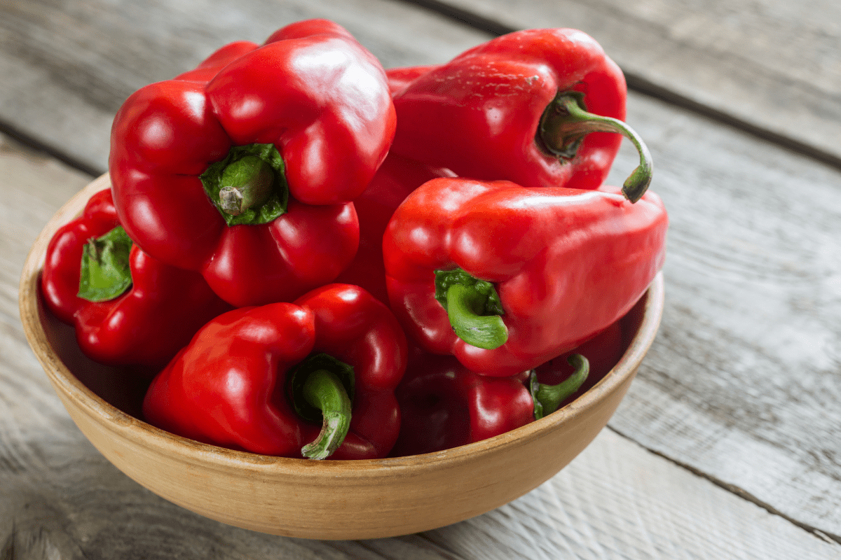 whole red bell peppers in bowl